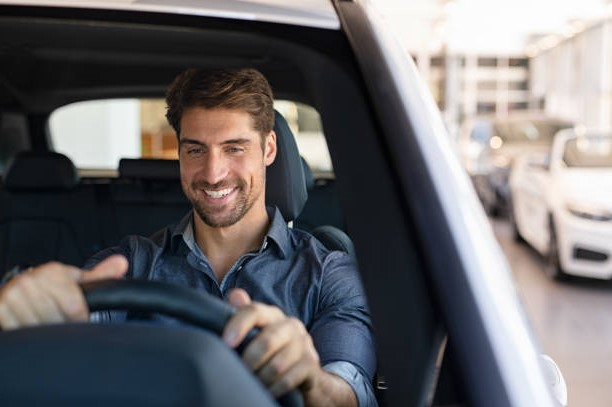 Young smiling man examining a new car in a showroom. Happy guy feeling comfortable sitting on driver seat in his new car at showroom. Man ready to make first test drive.